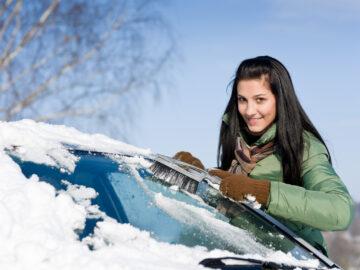 девушка чистит снег на автомобиле
