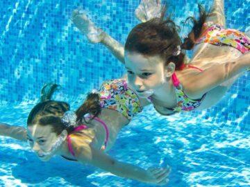 Девочки в купальниках плавают в бассейне