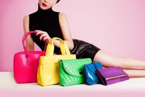 Девушка лежит на фоне разноцветных женских сумок